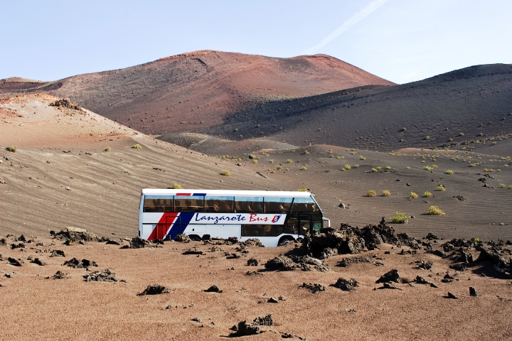 Busses follow the route of the Volcanoes through the badlands of Timanfaya National Park in Lanzarote, Spain
