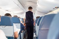 Interior of airplane with passengers on seats and steward walking the aisle. How to survive a longhaul flight