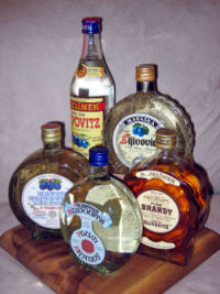 5 differently shaped bottles of Rakija grouped together. 1 tall bottle and 4 short round bottles