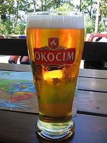 Glass with Okocim Lager on a table outdoor