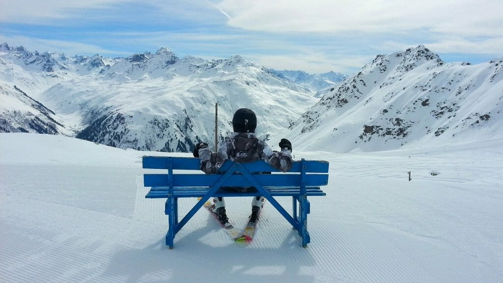 Person sitting with skis on blue bench in front of snowy ski slope and mountains in the distance