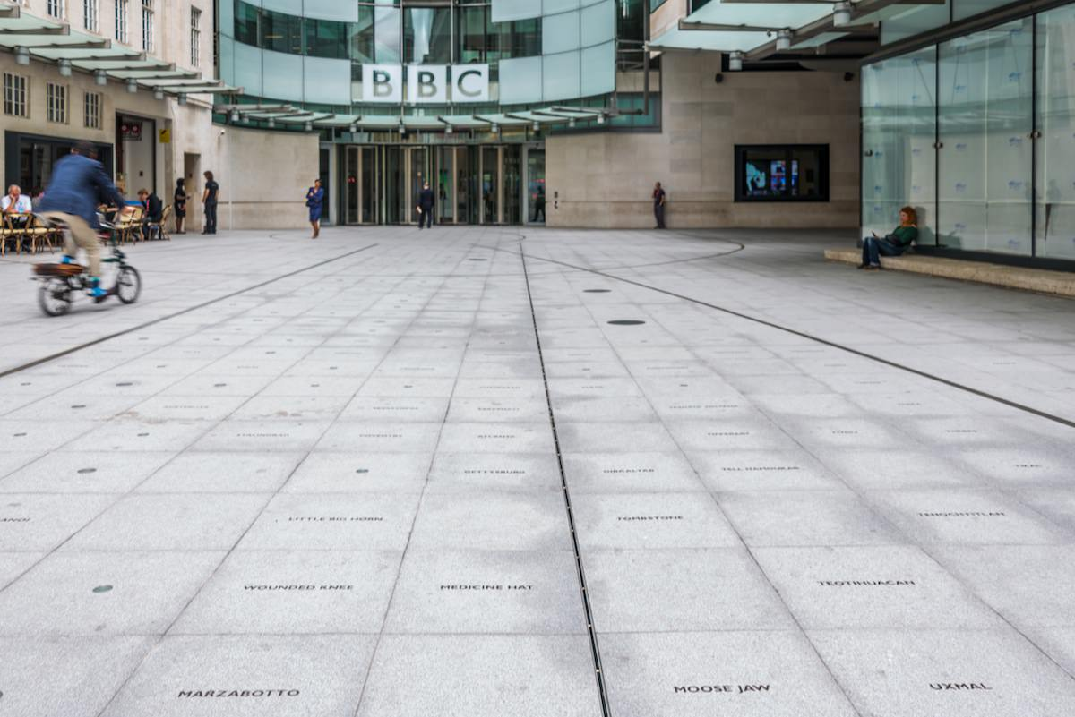 The entry courtyard to the BBC entrance. Small bronze plaques are inset into the concrete courtyard, memorializing places where atrocities and earth-shaking events have taken place in world history.