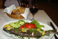 Whole fish with fresh tomatoes and cucumbers on a plate with a breadbasket and wine glass in the background