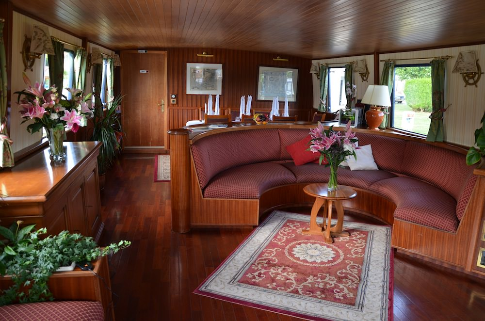 The lengthy saloon is undoubtedly the barge's centerpiece and meeting place, with a stained and polished wooden floor, glossy wood paneled walls, and slatted wooden ceiling