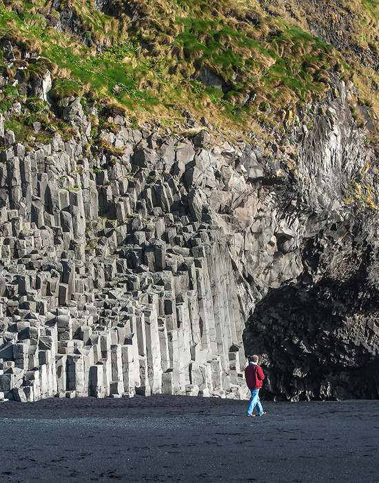 Behind the beach cliffs of hexagonal basalt columns soar overhead and caves penetrate the cliffs at sea level. They were formed from slow-cooling lava.