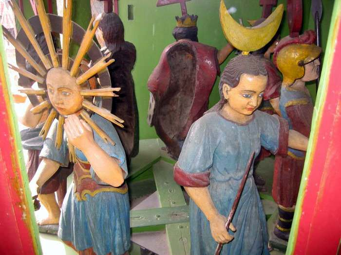 Inside the tower, the figures for Sunday and Monday await their turns to look out the window