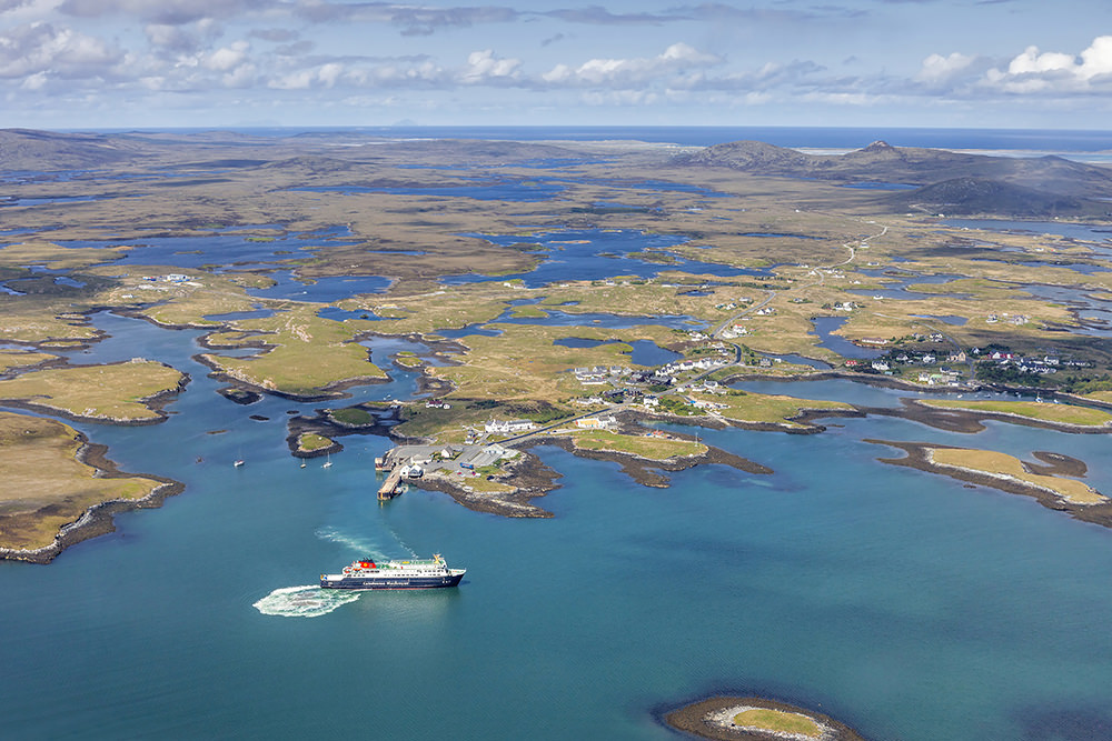 From above, Lochmaddy, the village capital of North Uist and the drowned eastern landscape of peat bogs and lochans — earth and water — stretching to the Atlantic coast in the distance. Once the haunt of pirates, it is now a special marine conservation area. (Courtesy: www.ruralnetwork.scot, © Peter Scott)