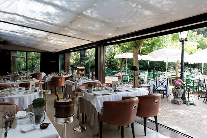 inside of a restaurant with white clothed tables with brown chairs and an open front to outside seating - Restaurant at the Hotel Cazaudehore Le Forestiere