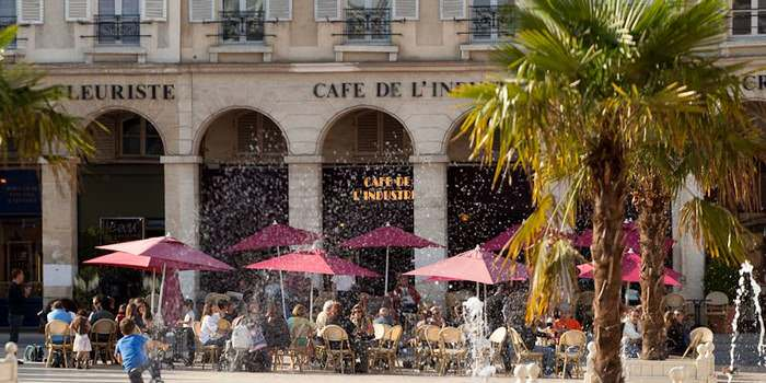 Central Square with water fountain and street cafe with red umbrellas, people enjoying a summer day at La Place du Marche in Ste. Germain en Laye