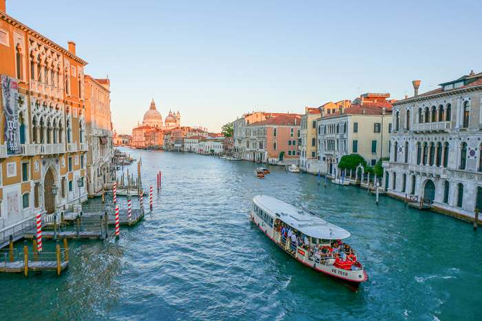 Vaporetto travels along the Grand Canal at sunset n Venice - Where to Stay in Venice