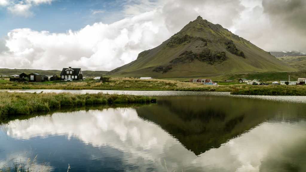 Black and white icelandic houses with a mountain in the background and a lake in the foreground