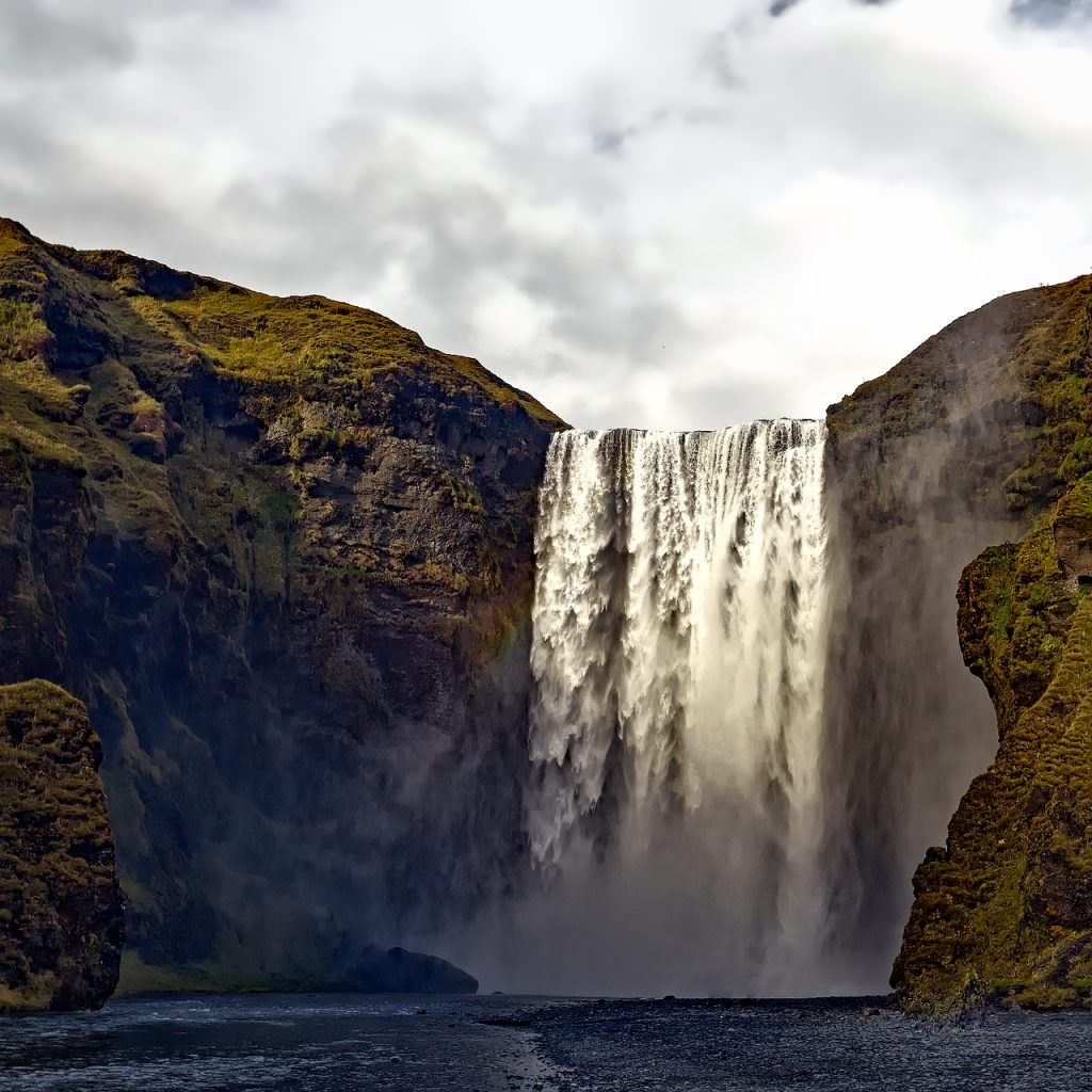 Skogafoss Waterfall Iceland - large waterfall from a tall cliff