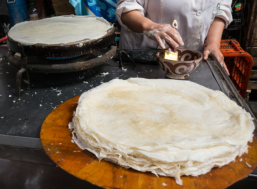 Moroccan Cooking School in Fes: Warka is thin, phyllo-like pastry cooked while you wait on the flat grill at left. The batter is painted onto the grill.