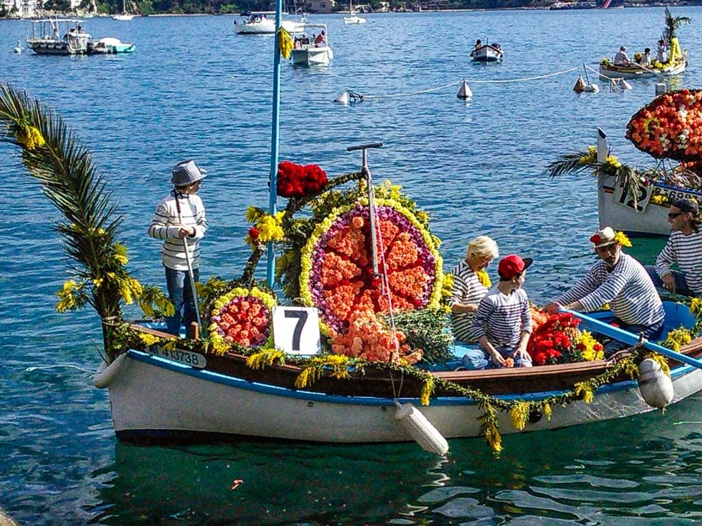 Beautifully decorated boats at the Battle of the Flowers in Villefranche-sur-Mer's Battle of the Flowers (Combat Naval Fleuri)