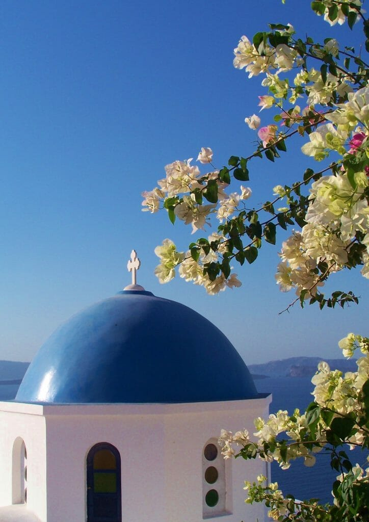 On a Trip to Santorini, the dome and white stucco of the Oia Santorini Church is a must see for the religious or secular