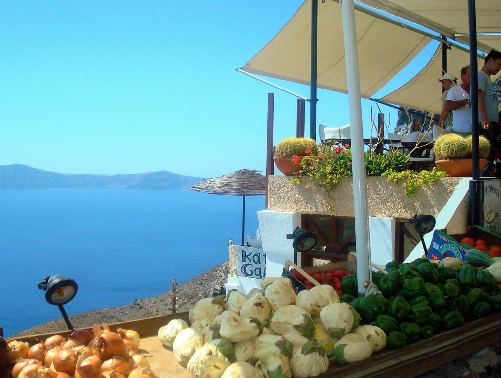 Produce displayed above an ocean view on a trip to Santorini