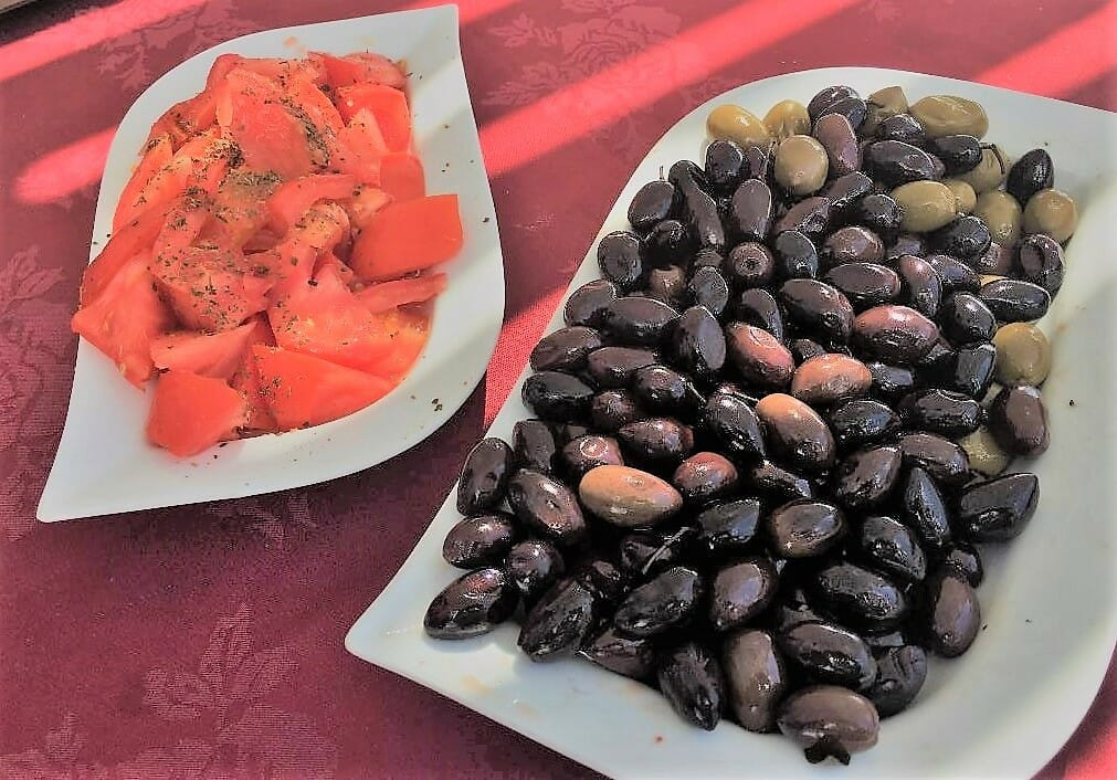 Santorini Day Tours exposed us to delicious Tomatoes and Greek Olives in separate white dishes on a red table cloth