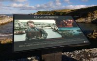 Tourist sign in Ballintoy Harbor with information about where Game of Thrones was filmed