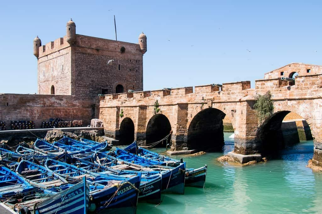 Blue boats in front of medieval bridge and tower in Essaouira Game of Thrones Film Location in Morocco