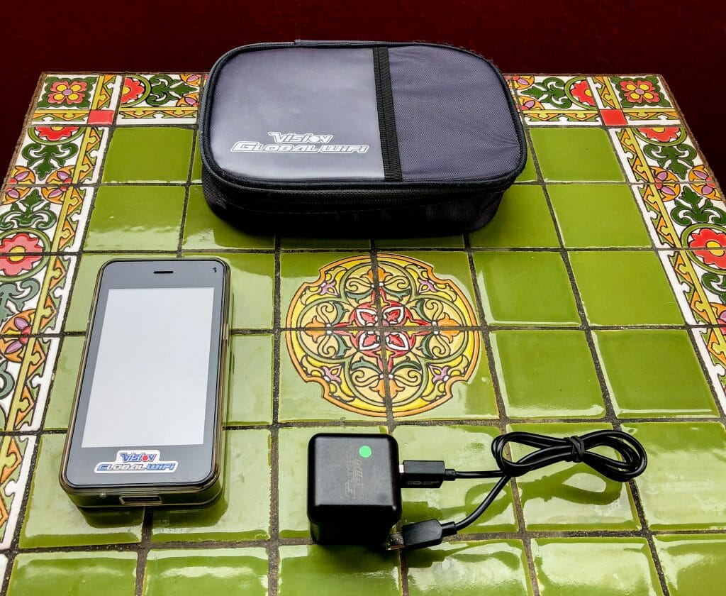 Green Tile table with Vision Global Wifi Package items on top, including Wifi device, charger and pouch