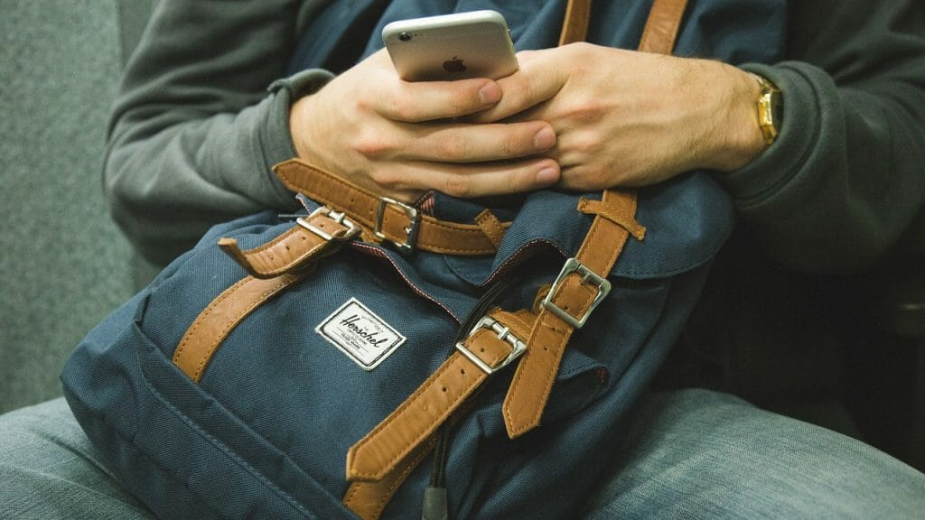 Man holding cell phone and backpack
