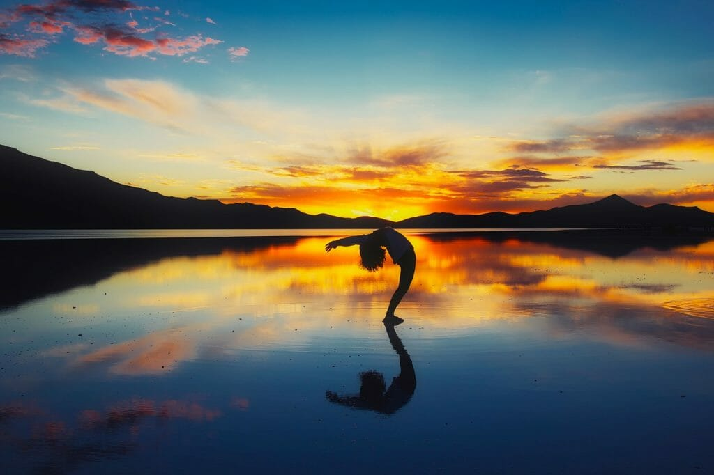 Woman doing a backbend on a beach at sunset