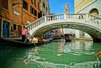 Gondolas gliding under the Rialto Bridge