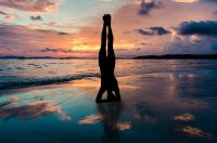 Woman doing handstand on the beach during sunset