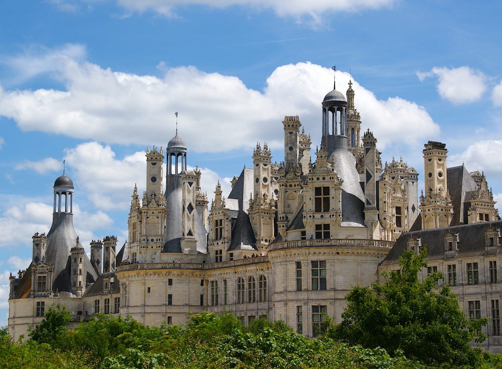 Beautiful french castle with many spires on sunny day with blue sky and stunning clouds