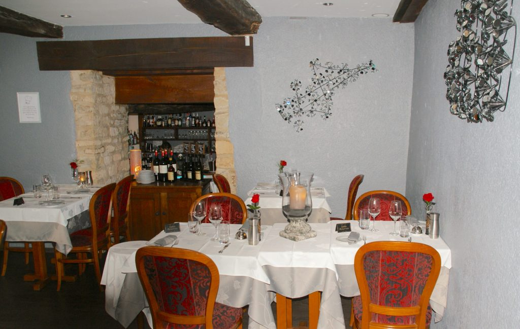 Cozy French Restaurant Interior - Tables with white table cloths, wood chairs, low ceiling with wood beams