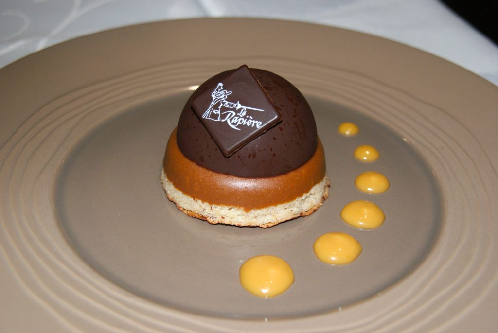 Amazing chocolate dessert, beautiful food design with yellow sauce on plate