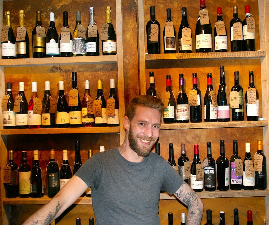 Man in front of lots of wine