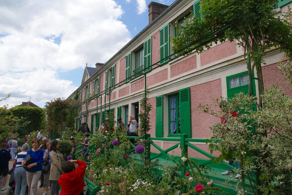 Monets house in Normandy - Pink house with green shutters and beautiful flowerbeds in front