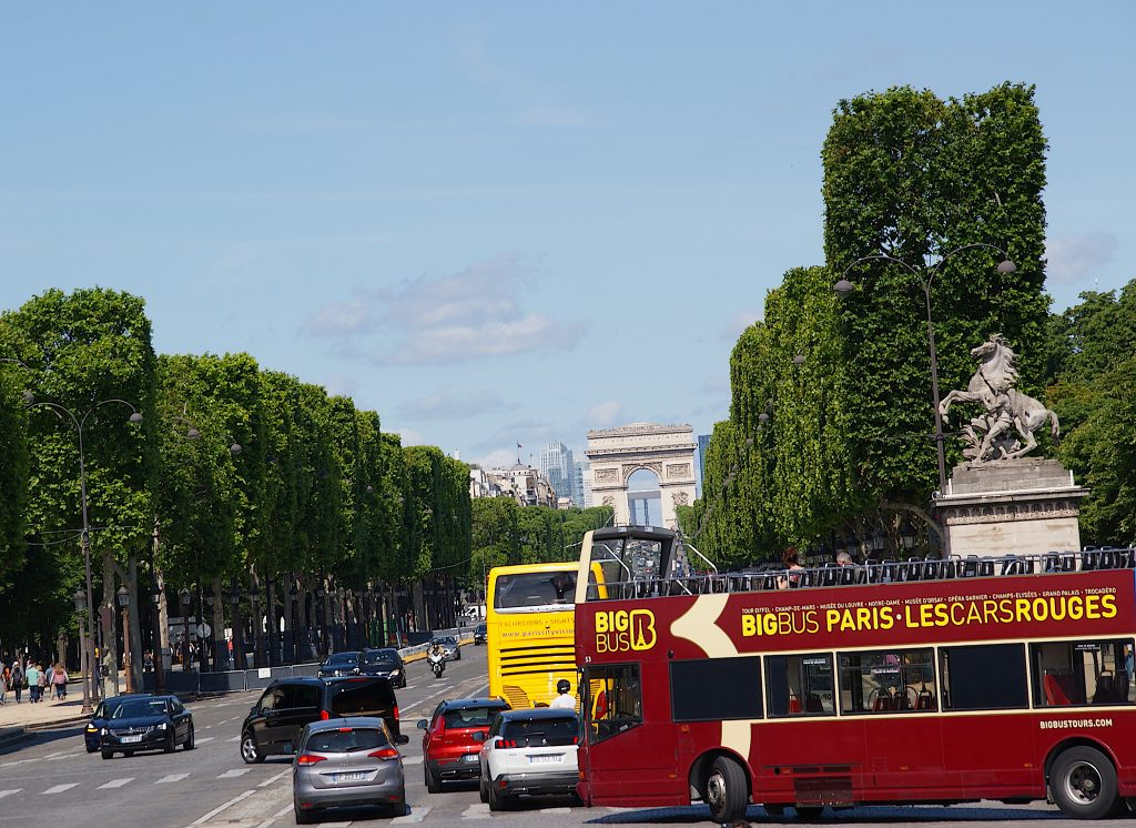 Red Big Bus for Hop-On-Hop-Off-Tours in front of the traffic of Paris