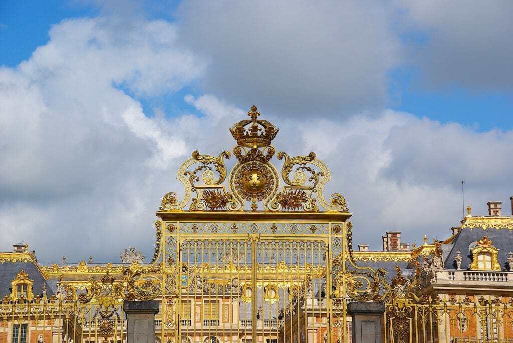The golden Palace of Versailles in front of a cloudy, blue sky