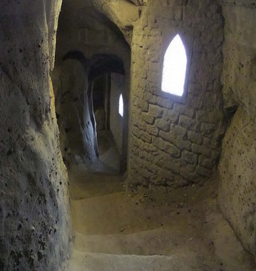 Caves underneath the castle with sunlight peaking into the sparse windows