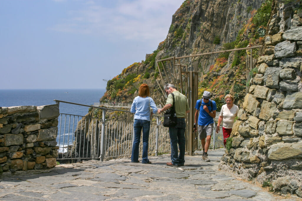 Entrance to Riomaggiore hiking trail in Cinque Terre - people walking on coastal hiking trail
