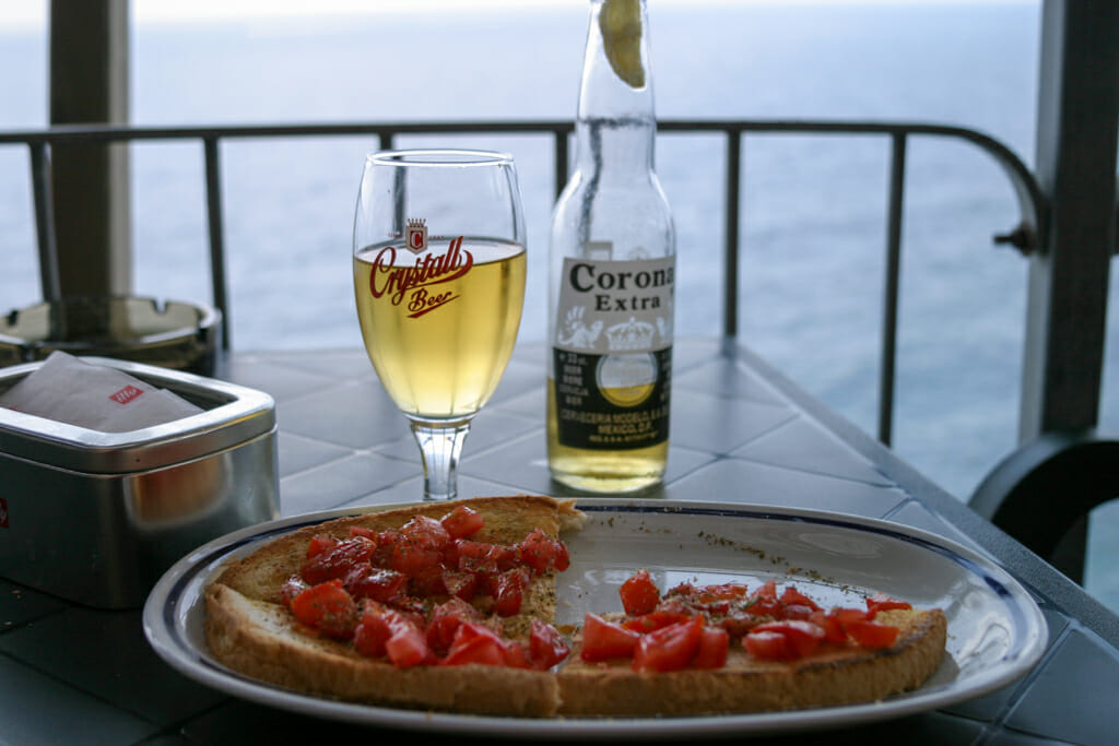 Bruscetta and beer on table overlooking the ocean
