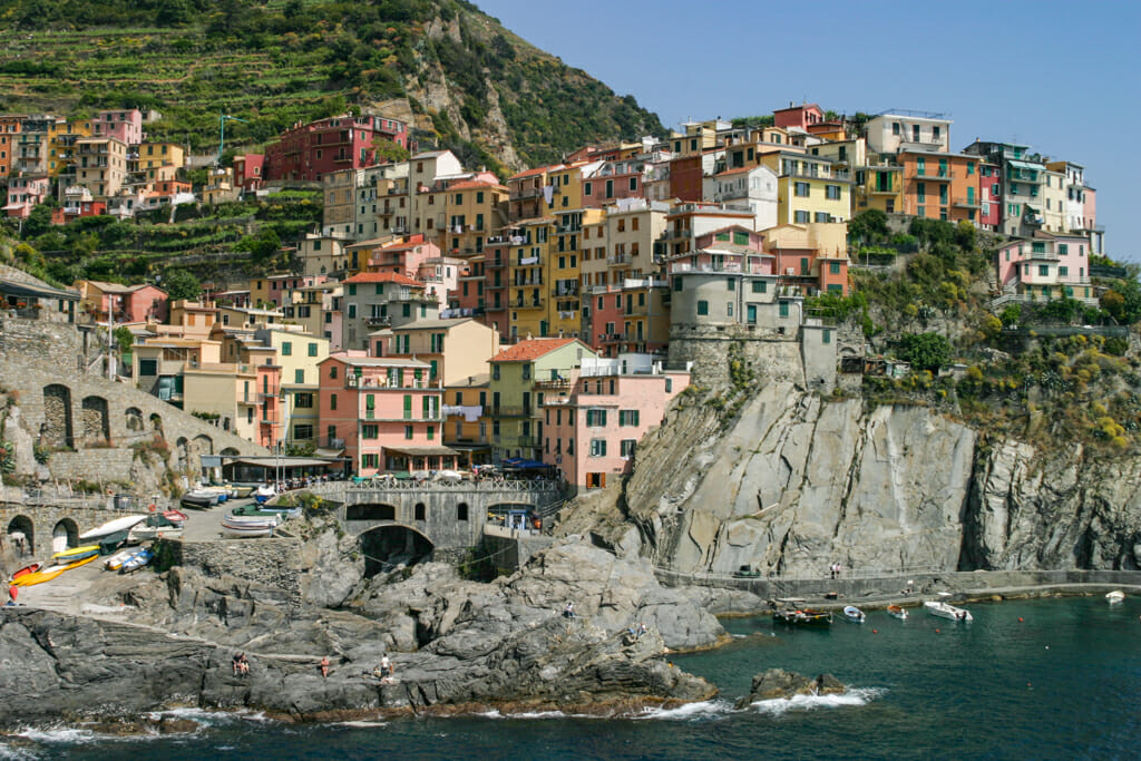 view of Manarola perched on the cliffs depicting a lifestyle with colorful buildings, swimmers, and boats in the cove.