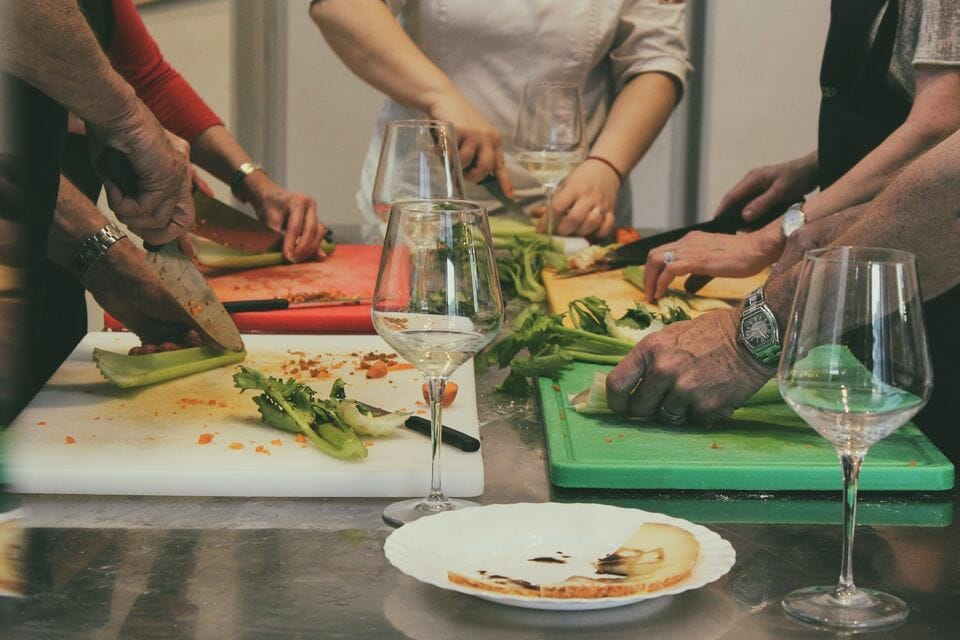 People around a table, chopping vegetables with wine glasses