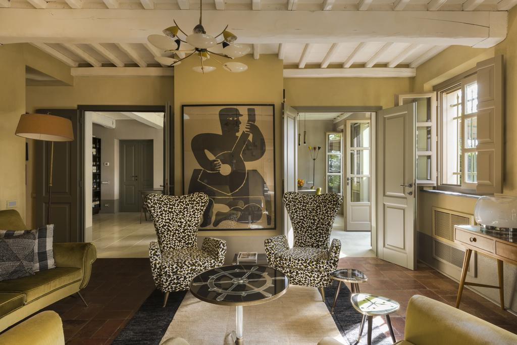 Inside of a suite at the Hotel Locanda al Colle with a painting of a guitar player, print chairs, and natural light