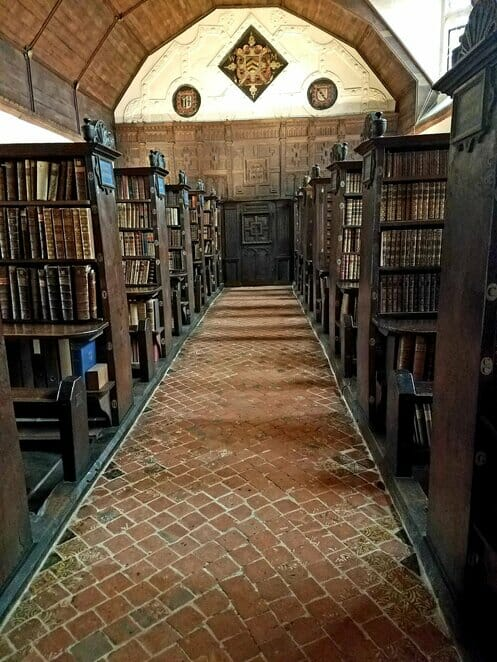 View down a main aisle with peaks of the chained books in Merton College Upper Library