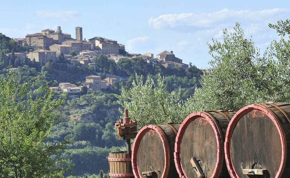 Wine barrels in front a picturesque italian town view