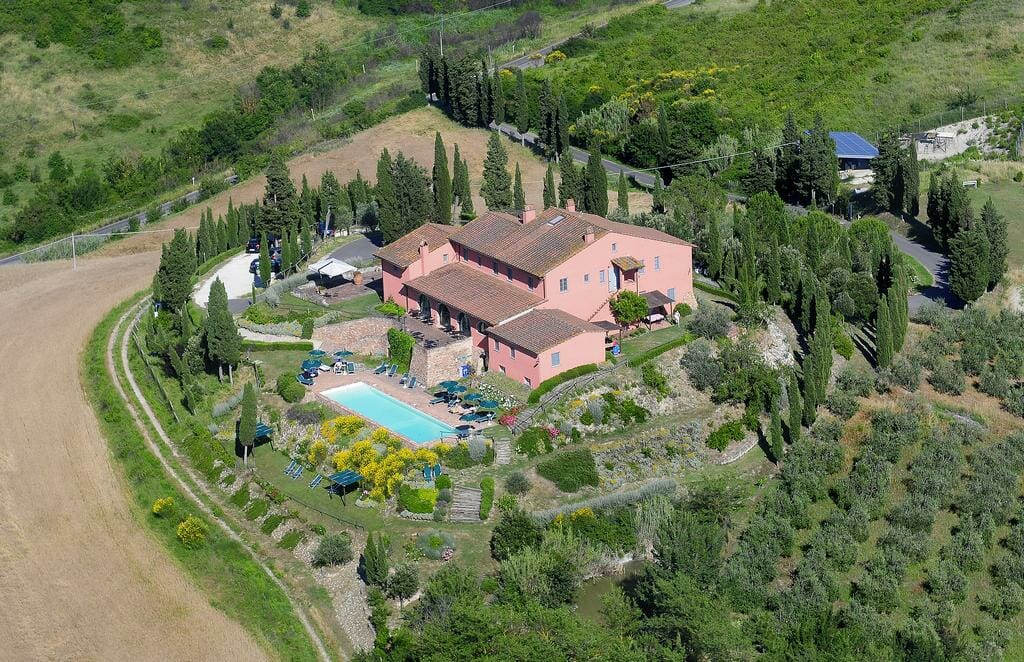 Aerial view of a luxurious villa with a mass of garden and a huge pool