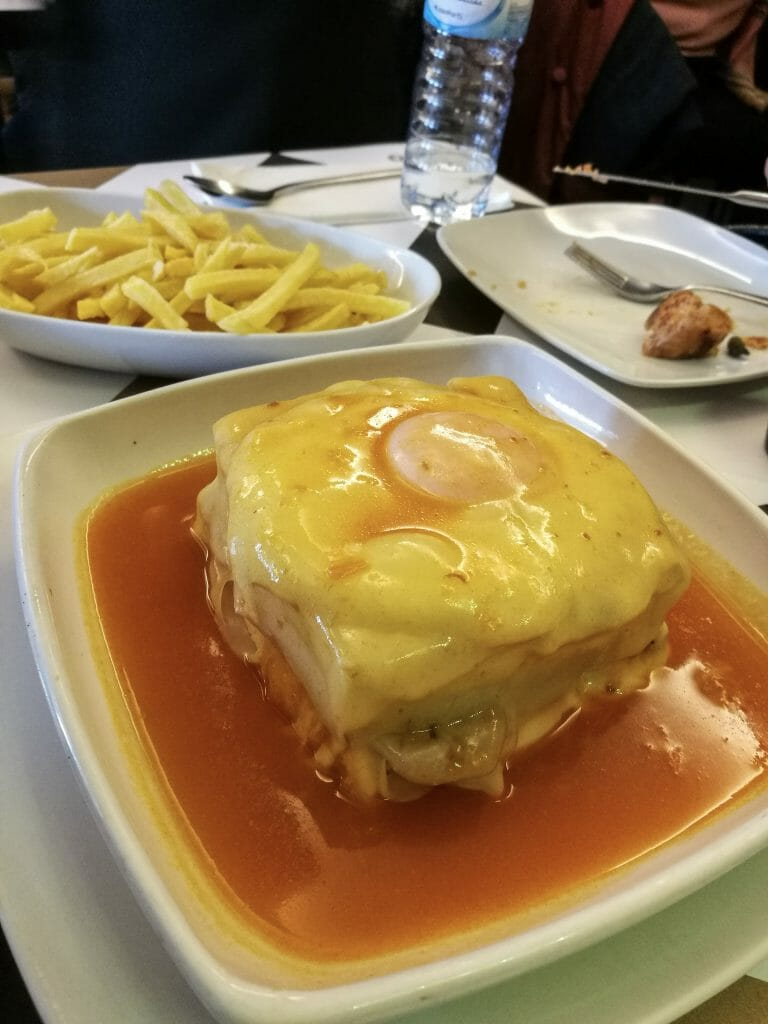 Steak and sausage sandwich topped with a fried egg and smothered in sauce with fries behind it