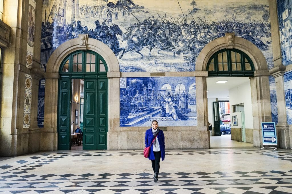 Woman standing in front of a court mural with a war mural above it in Sao Bento