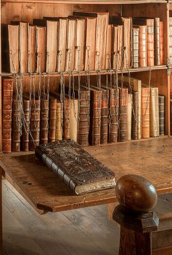 A book shelf of chained books with one pulled out, laying on the desk to read
