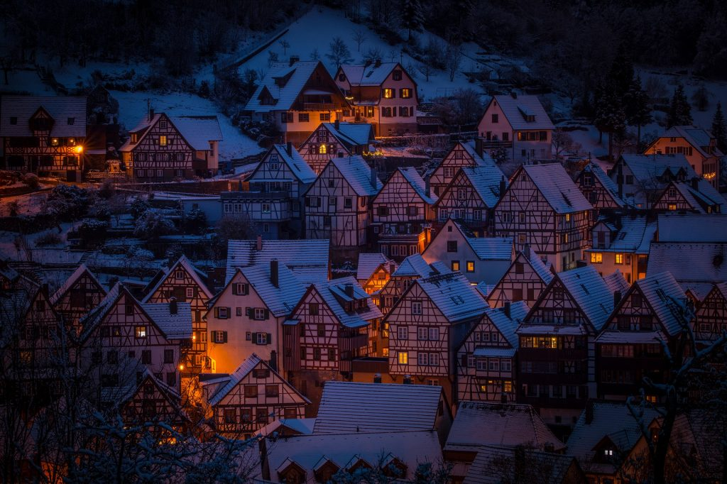Cluster of Austrian homes dusted with snow and glowing with lights