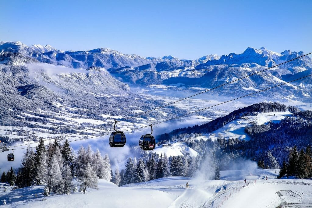 Ski lifts gliding over the perfect ski slopes surrounded by snow dusted pine trees