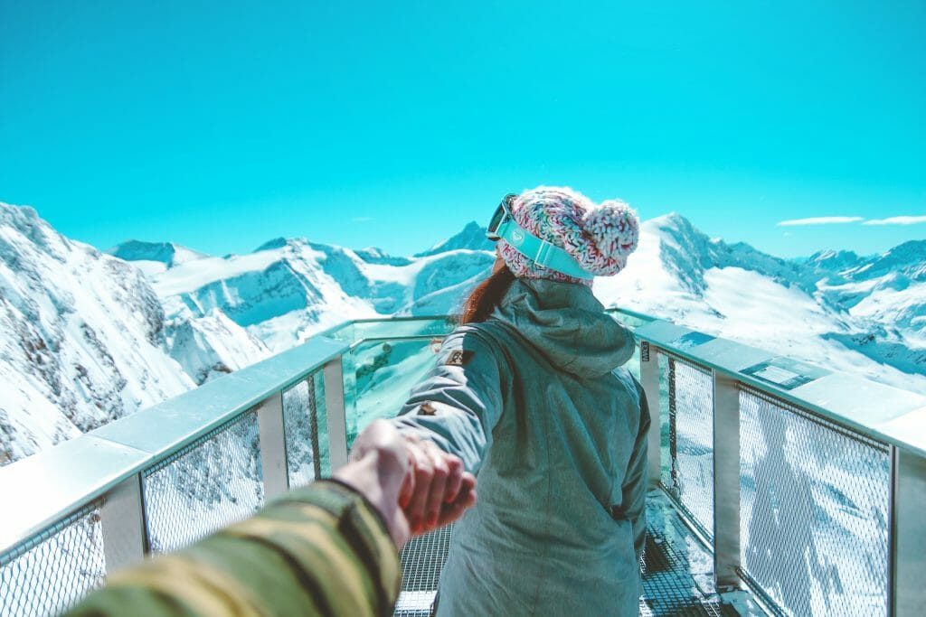 Woman in winter clothes reaching back for mans hand in front of snow capped mountains